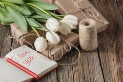我爱你在笔记本的词组有在桌上的花的 免版税图库摄影