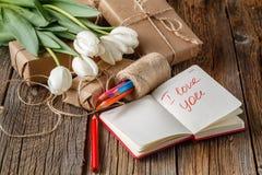 我爱你在笔记本的词组有在桌上的花的 库存图片