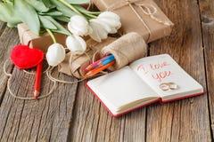 我爱你在笔记本的词组有在桌上的花的 免版税库存照片