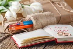 我爱你在笔记本的词组有在桌上的花的 图库摄影