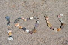 我爱你拼写与在海滩的小卵石 库存照片