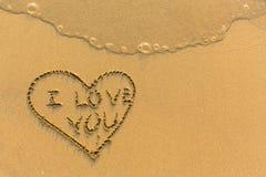 说我爱你的心脏-画在海滩沙子 免版税库存照片