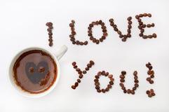 我爱你签字用咖啡豆和咖啡在白色b的 库存照片