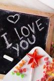 我爱你,写在有白垩的一个黑板,焦糖,糖果,星,鞭子,情人节,华伦泰,浪漫 免版税库存照片