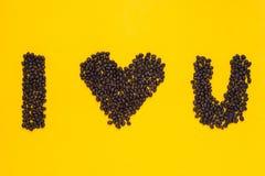 我爱你从咖啡豆的词在黄色背景 图库摄影