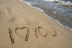 我爱你-在海滩沙子的题字 免版税库存图片