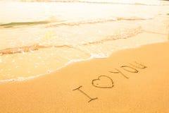 我爱你-在海滩沙子的题字 库存图片