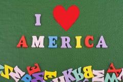 我爱在从五颜六色的abc字母表块木信件组成的绿色背景的美国词,复制广告文本的空间 库存图片
