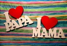 我爱妈妈和爸爸,在明亮的镶边背景的木词 免版税库存照片
