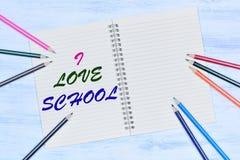 我爱学校 在笔记本的文本在一张木桌上 库存照片