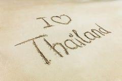 我爱心脏在海滩沙子写的泰国词 免版税图库摄影