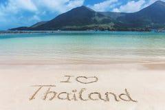 我爱心脏在海滩沙子写的泰国词 库存图片