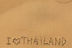 我爱泰国-在湿海海滩沙子的手工题字 摘要 免版税库存图片