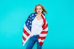 我爱的美国 拿着美国国旗和看照相机的牛仔裤和白色T恤杉的愉快的年轻微笑的妇女 免版税库存图片