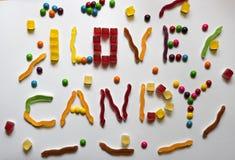 我爱糖果句子由不同的五颜六色的甜点做成在白色背景 图库摄影