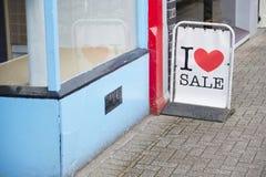 我爱销售在街道路面外部商店的标志板有爱心脏的 免版税库存图片
