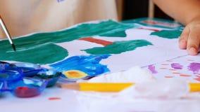 我的儿子绘一棵树,山,在他画他自己与油漆刷和调色板的图片的草 股票视频