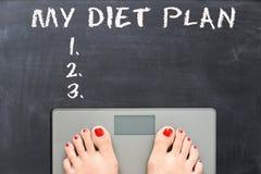我的在黑板的饮食计划有在重量等级的妇女脚的 免版税库存图片