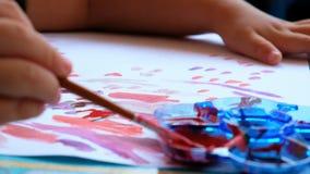 我的女儿在纸绘对学会艺术性与油漆刷和调色板 影视素材