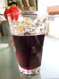 我的杯与草莓装饰的红葡萄酒coctail在桌上 免版税库存图片
