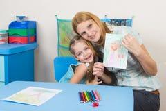 我的母亲和五岁的女儿拥抱和展示绘了a 免版税库存图片