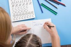我的母亲帮助孩子拼写字母表,一张顶视图 免版税库存图片