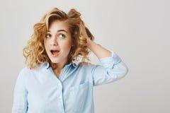 我的美发师是意想不到的 演播室射击了有看的卷发的逗人喜爱的女性白种人女孩接触它和在旁边 图库摄影