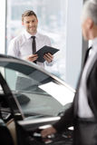 我知道您会想要这辆汽车。英俊的年轻经典汽车推销员 免版税库存图片