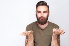 我穿上` t知道!迷茫的有胡子的人画象有深绿T恤杉的反对浅灰色的背景 库存照片