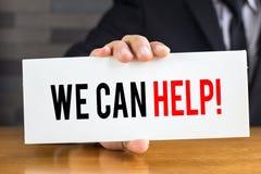 我们可以由商人帮助,在白色卡片的消息和举行 免版税库存图片