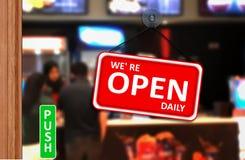 我们是在商店玻璃门的开放每日标志 免版税库存图片