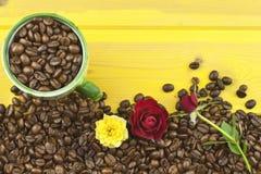 我们爱咖啡 基于咖啡的玫瑰 咖啡豆,倒在黄色木桌上 图库摄影