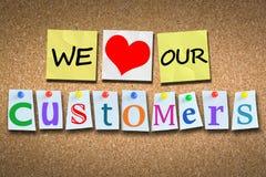 我们爱我们的木黄柏广告牌的顾客与有色的别针 免版税库存照片