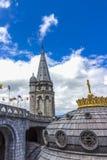我们的不同的国家念珠和旗子的夫人大教堂反对蓝天的 卢尔德,法国 库存图片