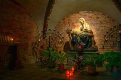 我们的哀痛的夫人,圣母怜子图雕象在一个黑暗的教堂里 免版税库存照片