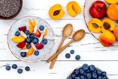 戒毒所和健康superfoods早餐碗概念 素食主义者椰奶chia播种在土气桌的布丁用各种各样的果子 图库摄影