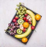 戒毒所和饮食食物概念、新鲜水果、香蕉、葡萄、猕猴桃和蜜桔,草莓排行了葡萄酒木箱顶视图 免版税库存照片