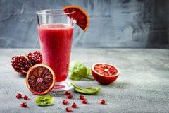 戒毒所新鲜的汁液或圆滑的人在玻璃用血橙,绿色,石榴 自创刷新的果子饮料 复制空间 免版税库存照片