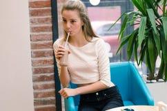 戒毒所汁液和圆滑的人健康营养的 坐在咖啡馆的美丽的微笑的妇女用在瓶和drin的新鲜的戒毒所汁液 库存照片