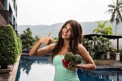 戒毒所饮食:外面年轻美好的女孩standig用硬花甘蓝和红辣椒 免版税库存照片