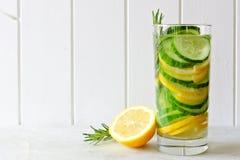 戒毒所水用柠檬、黄瓜和迷迭香在白色木头 免版税库存照片
