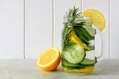 戒毒所水用柠檬,黄瓜,在白色木头的瓶子 免版税库存照片
