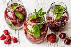 戒毒所水用莓,草莓,在白色木背景的樱桃 喝健康 免版税图库摄影