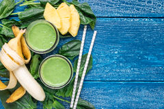 戒毒所绿色圆滑的人用菠菜、菠萝、香蕉和酸奶,平的位置,拷贝空间 免版税图库摄影