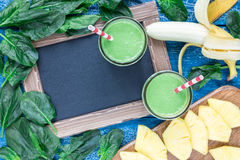 戒毒所绿色圆滑的人用菠菜、菠萝、香蕉和酸奶,顶视图,拷贝空间 免版税库存照片