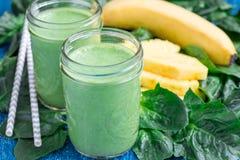 戒毒所绿色圆滑的人用菠菜、菠萝、香蕉和酸奶 免版税库存图片