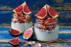 戒毒所superfoods用早餐或健康点心-与格兰诺拉麦片和新鲜的无花果的酸奶在蓝色木背景的玻璃瓶子 库存照片
