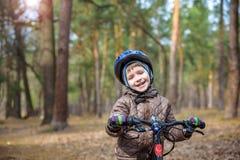 3或5年的愉快的孩子男孩获得乐趣在有a的秋天森林 免版税库存照片
