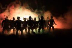 战争概念 与在战争雾天空背景,世界大战在多云地平线下的战士剪影的军事剪影场面战斗在 库存照片