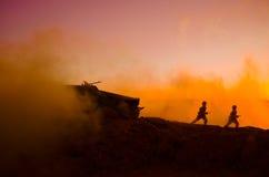 战争概念 与在战争雾天空背景,世界大战在多云地平线下的战士剪影的军事剪影场面战斗在 免版税库存图片